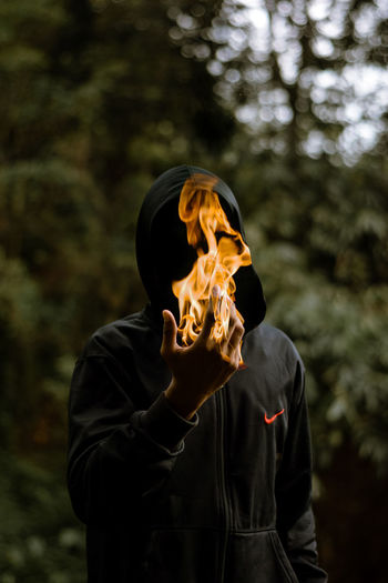 Full length of man holding burning outdoors