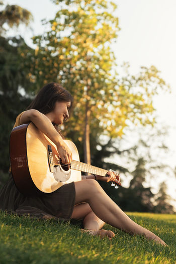 Young woman playing guitar on field