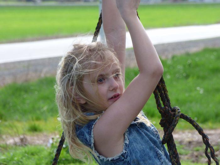 Close-up of cute girl swinging at park