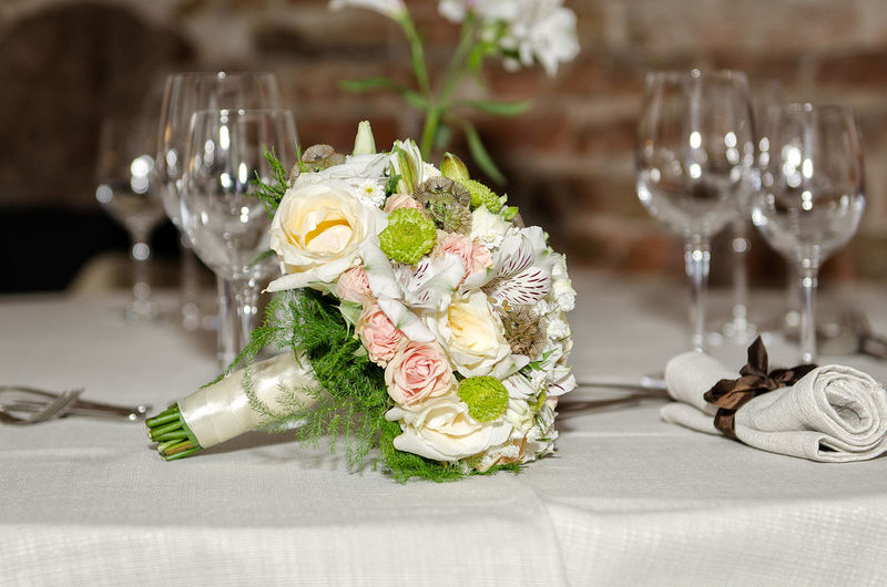 On the table stands bridal bouquet and champagne glasses. Bouquet Bride Celebration Celebration Event Ceremony Champagne Champagne Flute Close-up Drinking Glass Elégance Flower Flower Head Focus On Foreground Indoors  Life Events Married Place Setting Rose - Flower Table Wedding Wedding Ceremony White Color Wineglass