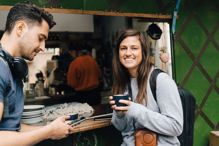 Smiling young woman using smart phone while standing on laptop