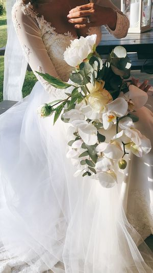 High angle view of people holding bouquet of white flowers