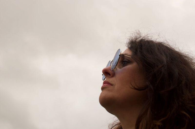 Woman in sunglasses looking away against sky
