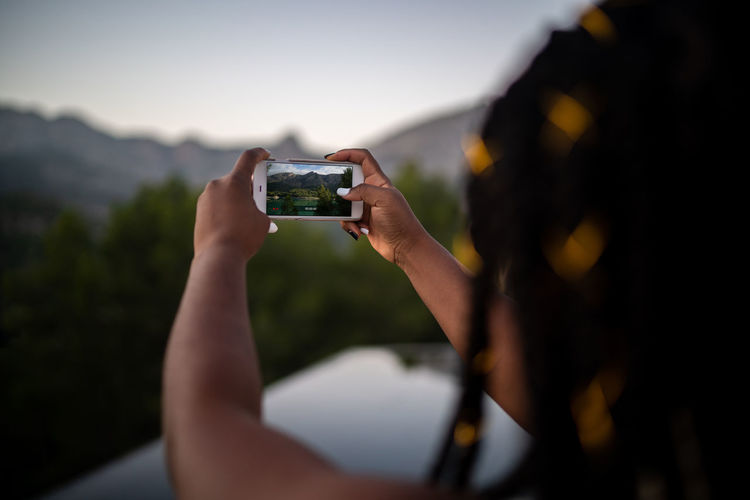 Close-up of person photographing mobile phone outdoors
