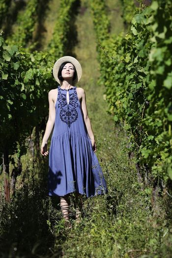 Full length of young woman standing in vineyard