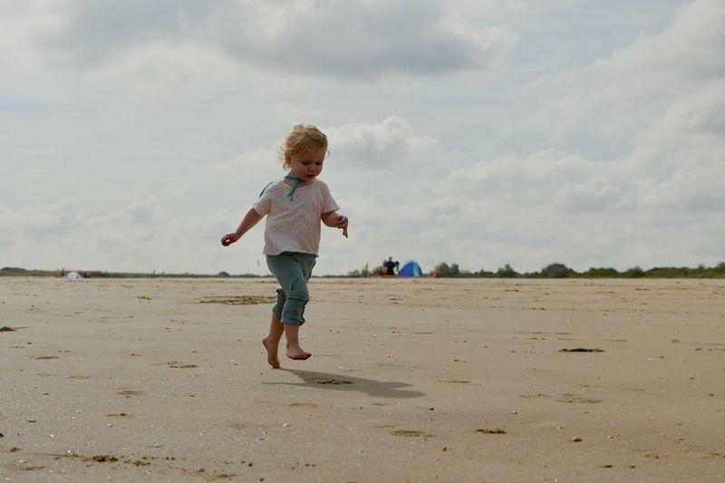 Full Length Of Girl Running At Beach Against Sky