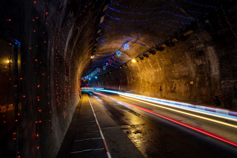 Light trails on road in illuminated tunnel