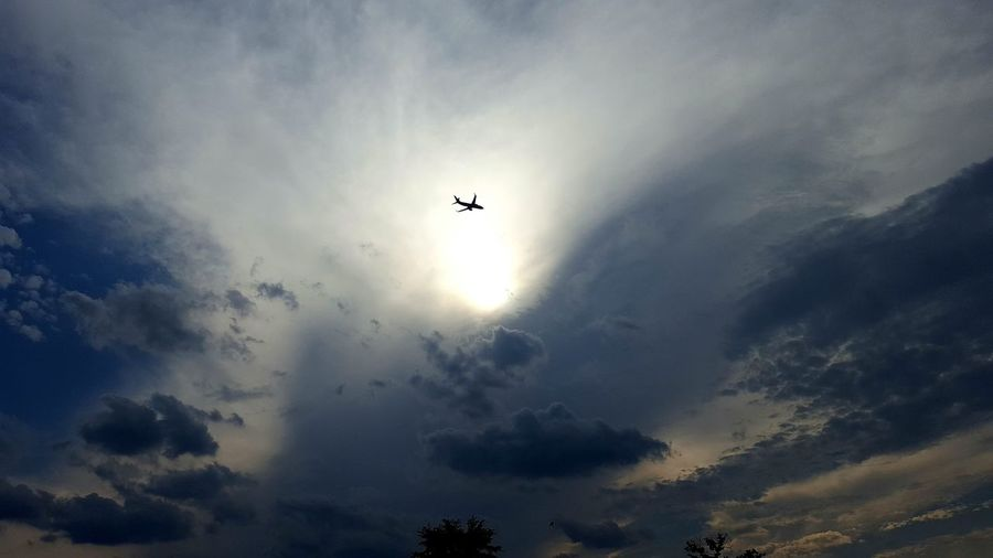 Low angle view of silhouette plane flying against cloudy sky
