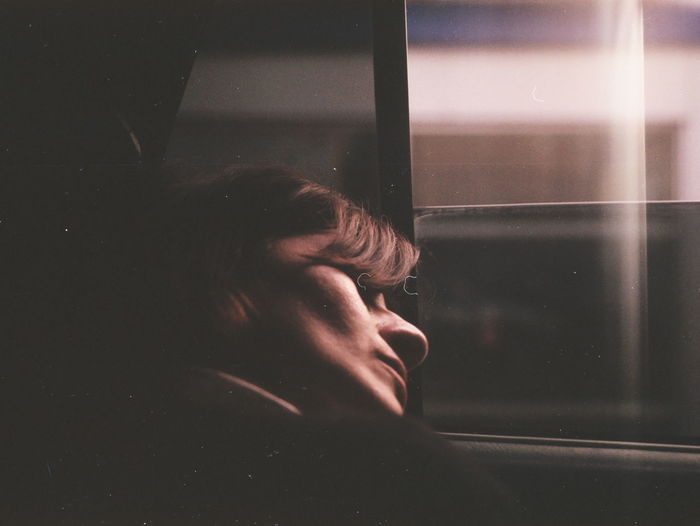 Close-up of woman sleeping by window