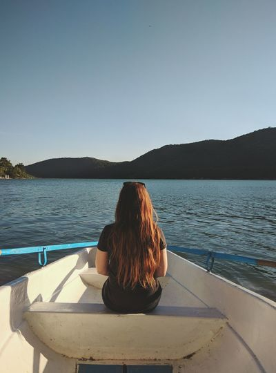 Rear view of woman sitting in rowboat on lake