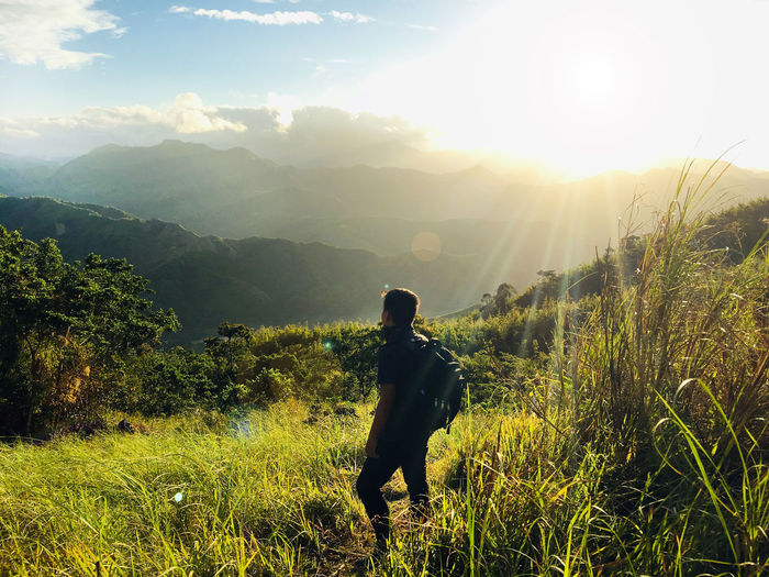 Beauty In Nature Plant Sky Mountain Real People Nature Scenics - Nature One Person Tranquil Scene Land Tranquility Sunlight Environment Landscape Grass Lifestyles Field Growth Leisure Activity Non-urban Scene Lens Flare Mountain Range Outdoors