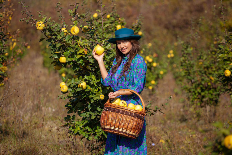 Portrait of woman picking fruits from plants