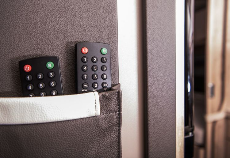 Close-up of remote controls against wall at home