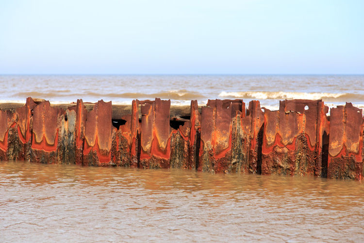 View of rusty posts in sea