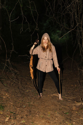 Hunter Archery Bare Tree Casual Clothing Field Forest Front View Full Length Hunting Land Leisure Activity Lifestyles Nature Night One Person Outdoors Plant Portrait Real People Smiling Tree Warm Clothing Wild Wildlife Women