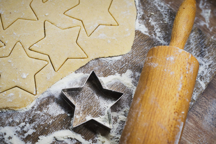 High angle view of star shape cookies with rolling pin and cutter on table