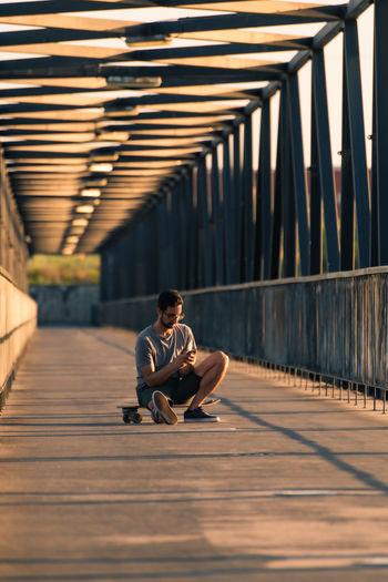 Man sitting on footpath at bridge