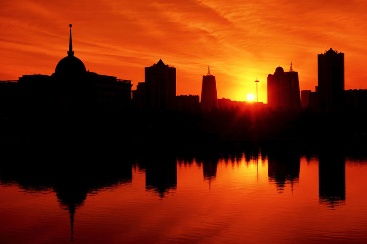 Silhouettes-on-Ishim Astana City Kazakhstan Architecture City Cityscape Eveining No People Orange Color Silhouette Sky Sunset Urban Water The Traveler - 2018 EyeEm Awards