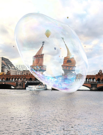 Digital composite image of bubbles and river against sky