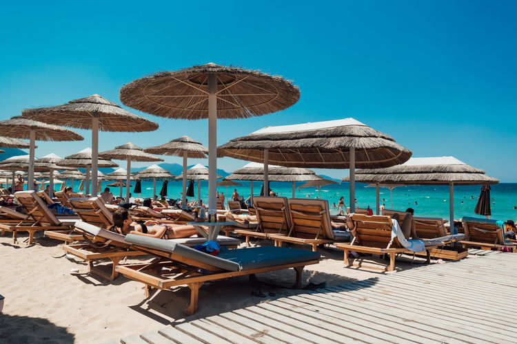 Chairs and tables on beach against clear blue sky