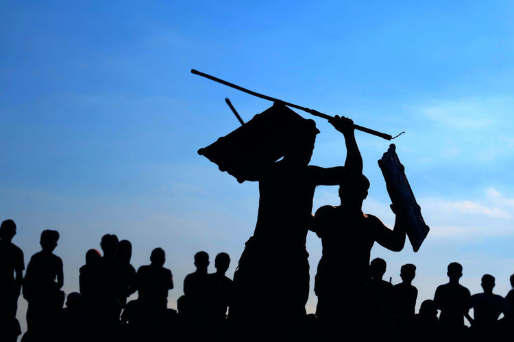 Silhouette men fighting in front of crowd against blue sky