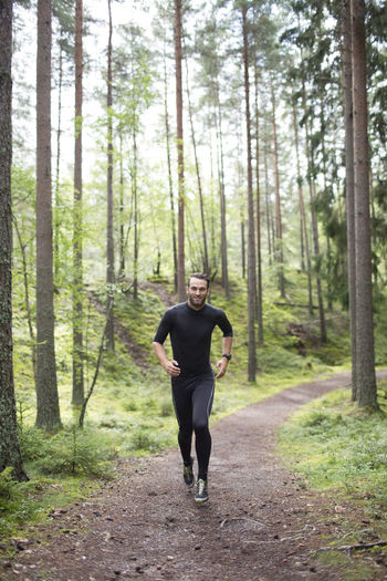 Full length of man running on footpath in forest