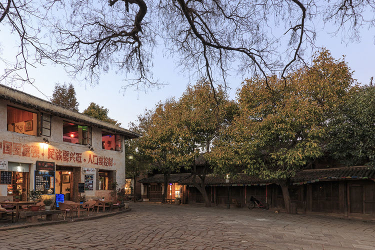 Shaxi, China - February 21, 2019: Central square of Shaxi old town at sunset Shaxi China ASIA Yunnan Yunnan ,China Market South Silk Road Tea Horse Road Minority Ethnic Group Old Town Kunming, China Landscape People Night Teather Old