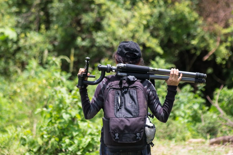 Rear view of woman carrying tripods in forest