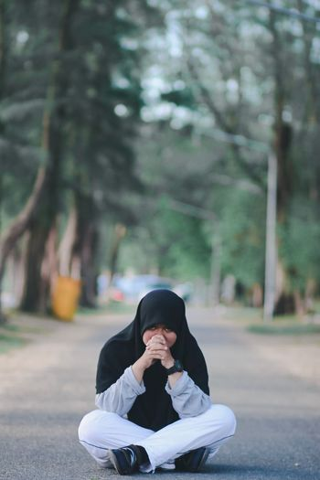 Portrait of young woman wearing hijab sitting on road