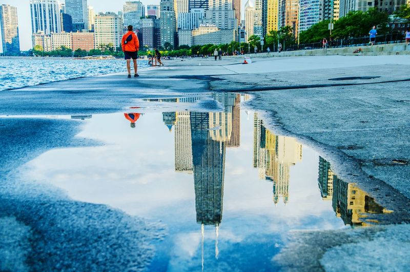 Reflection Of John Hancock Center And Buildings On Puddle At Shore In City