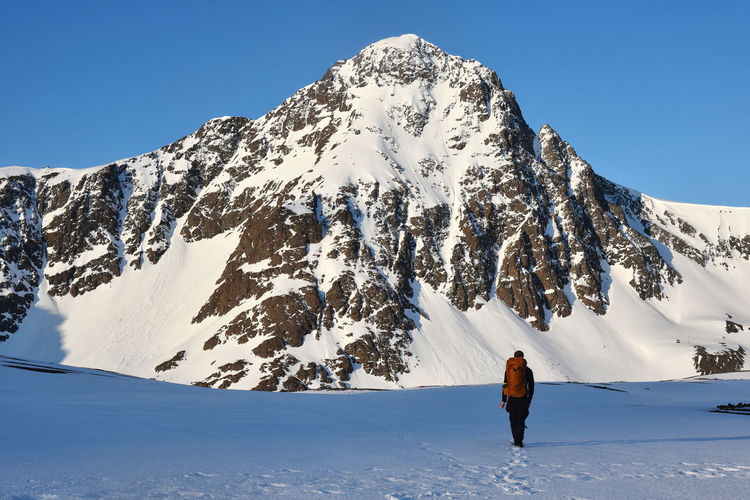 Rear view of person walking on snow covered mountain against sky