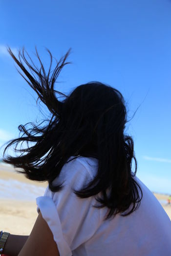 Portrait of woman with hair against blue sky