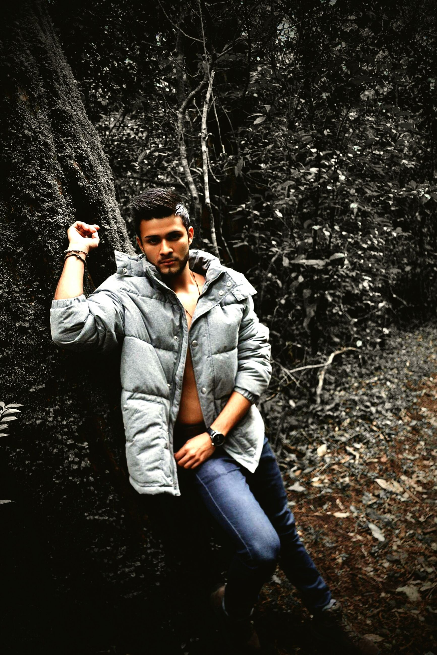 casual clothing, lifestyles, person, young adult, leisure activity, front view, looking at camera, standing, portrait, tree, full length, jacket, young men, forest, three quarter length, holding, smiling