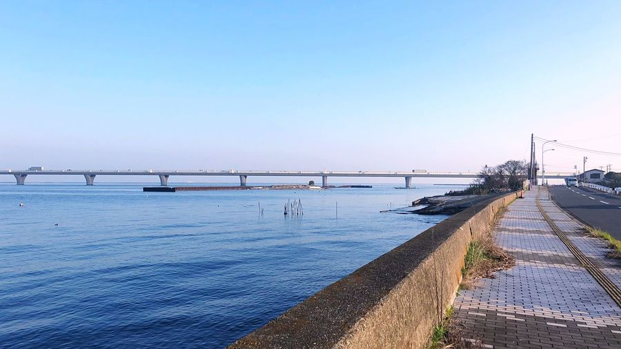 Bridge over calm sea against clear sky