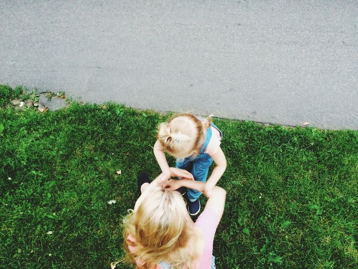 Directly above shot of mother with daughter on grass