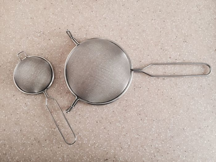 Close-up of sieves on table