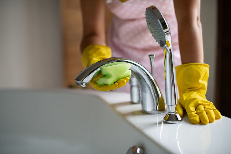Midsection of man holding faucet in bathroom