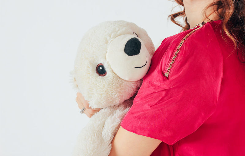 Midsection of woman holding toy against white background