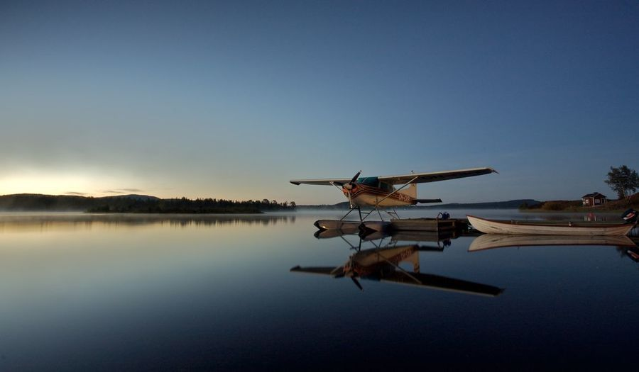 Airplane flying over lake against clear blue sky