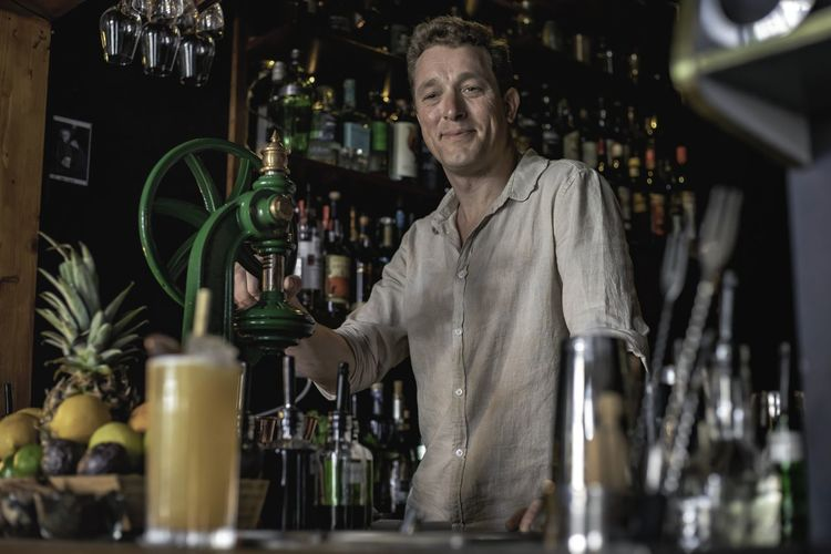 Portrait of a man standing in front of bar