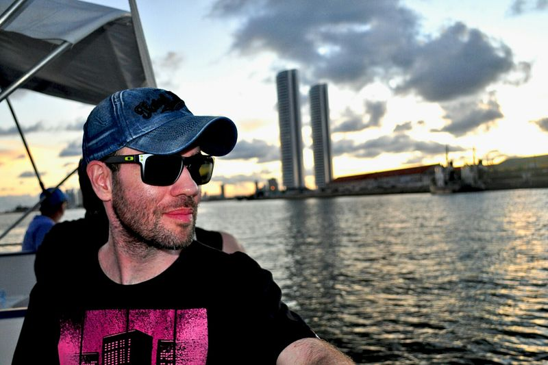 Man Wearing Sunglasses In Boat On Lake During Sunset