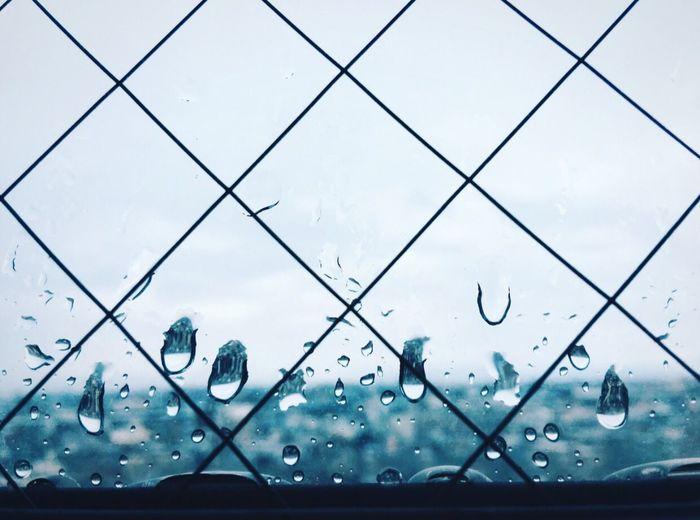 Wet Glass Window Against Sky