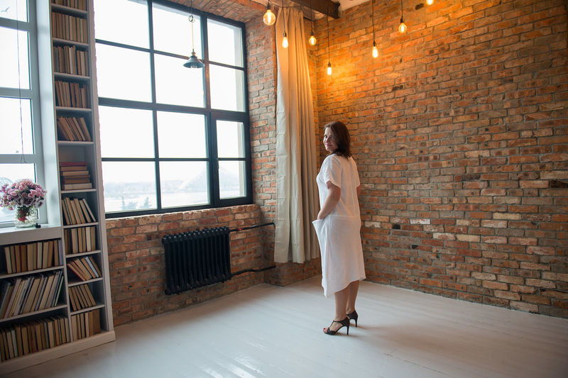 Portrait Of Woman Standing In Illuminated Room