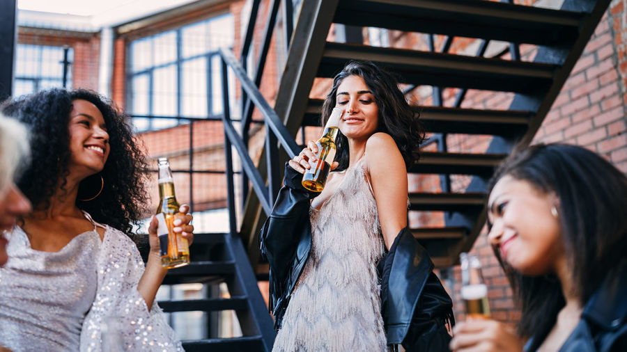 Happy friends holding beer bottle while standing outdoors