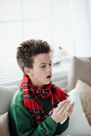 Boy looking away while sitting on sofa at home