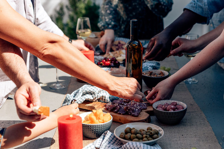 People outdoor picking up food appetizer tapas from a long table with a glass bottle of wine.