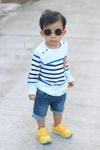 Portrait of cute boy standing on footpath