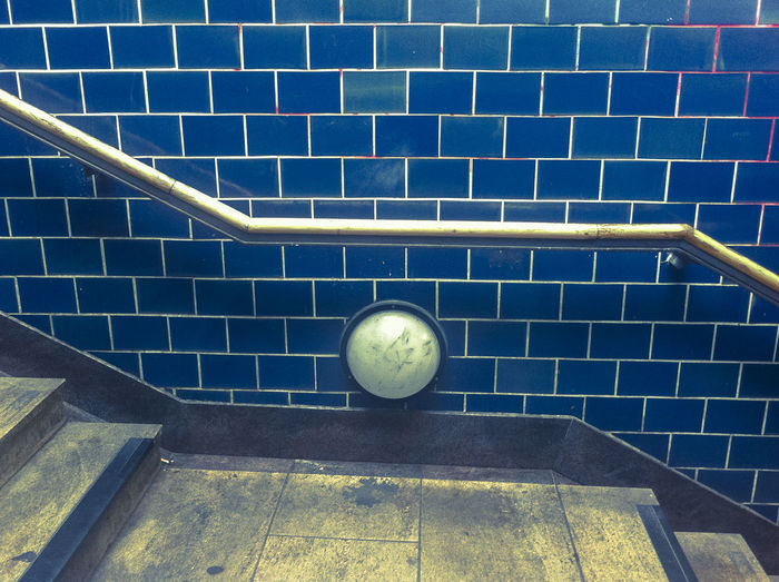 Staircase against blue brick wall