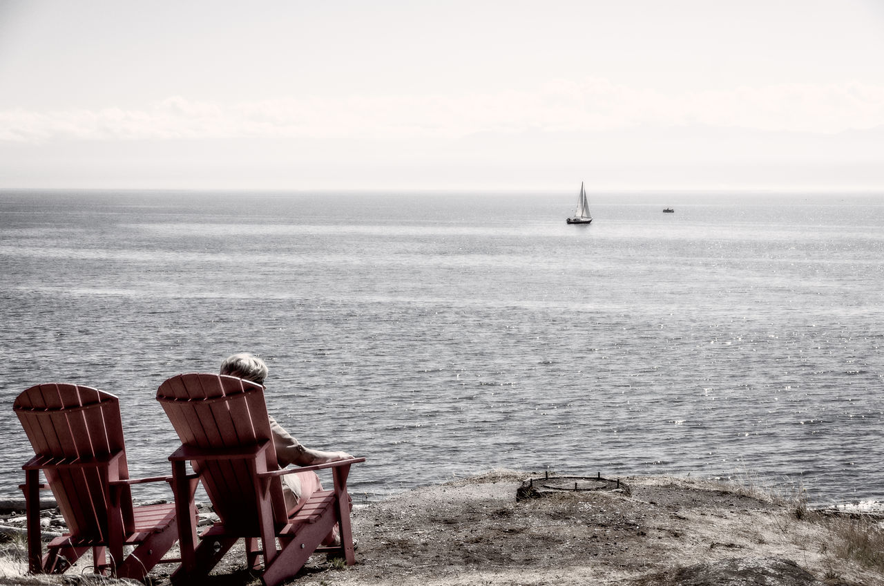 sea, horizon over water, water, nature, tranquility, rear view, tranquil scene, beauty in nature, scenics, beach, chair, sky, day, real people, outdoors, leisure activity, sand, vacations, men, one person, people