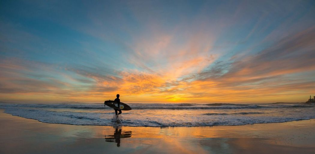 Silhouette man with surfboard walking in sea at beach during sunset